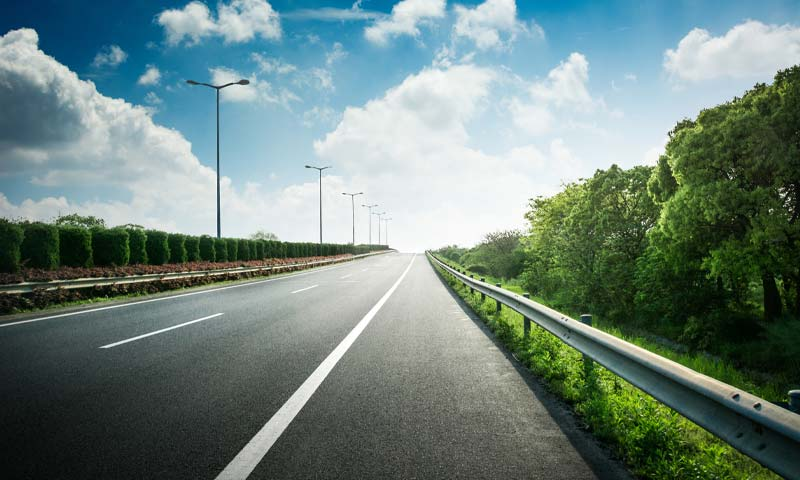 empty highway with trees lining both sides and blue sky in background